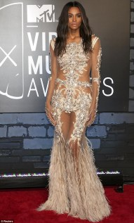 Ciara poses on the red carpet in sheer feathered dress at the 2013 MTV VMAs in New York